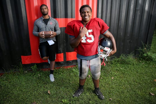 Hughes High School running back Keion Hinton, front, and head coach Chris Mobley formed a close bond as Hinton enters his freshman season for the Big Red, Wednesday, Aug. 28, 2019, in Cincinnati.