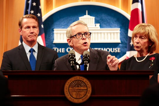 Ohio Gov. Mike DeWine delivers a statement with Lt. Gov. Jon Husted, left, and First Lady Fran DeWine, right, following the Dayton Mass Shooting on Tuesday, Aug.  6, 2019 at the Ohio Statehouse in Columbus, Ohio.  Facing pressure to take action after the latest mass shooting in the U.S., DeWine urged the GOP-led state Legislature Tuesday to pass laws requiring background checks for nearly all gun sales and allowing courts to restrict firearms access for people perceived as threats. (Joshua A. Bickel /The Columbus Dispatch via AP)