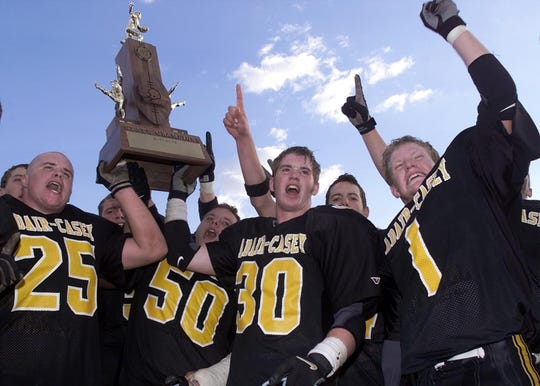Adair-Casey won the first two Iowa 8-player state championships, in 2000 and 2001. From left, A-C's Brady Carney, Neal Siedelmann and  Jared Uhlman celebrate their second consecutive 8-player state football crown.