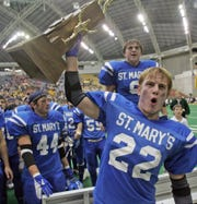 Remsen St. Mary's player Jeremy Galles leads his teammates in celebration. The Knights won the 8-player state football championship in 2004.