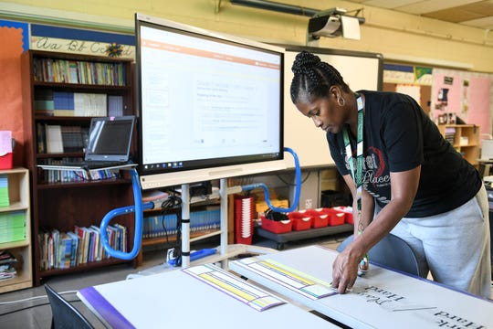Fifth grade teacher Adriane Blair puts down cursive writing examples onto the desks during preparations for the start of the school year at Chrysler Elementary School in Detroit, Wednesday.