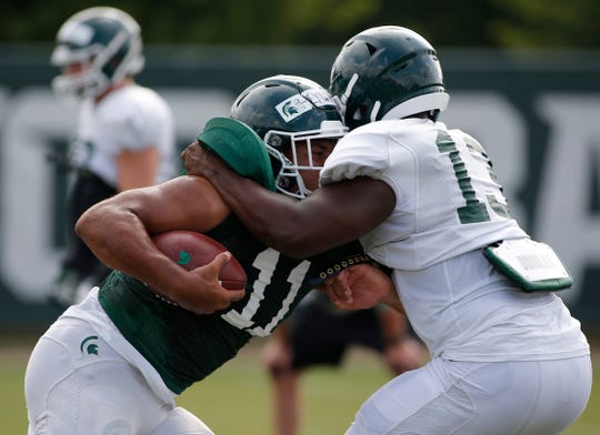 Michigan State running back Connor Heyward bangs into linebacker Marcel Lewis during a drill.