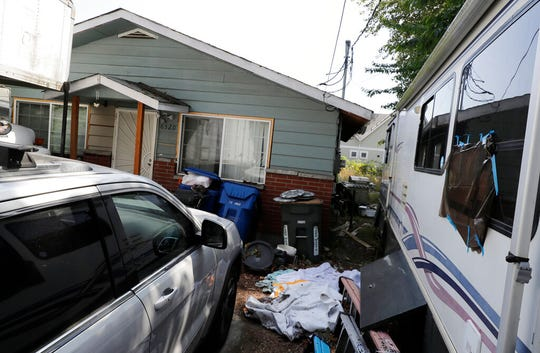 "In this July 31, 2019, file photo vehicles are parked outside the home of Paige A. Thompson, who uses the online handle ""erratic,"" in Seattle. Thompson was arrested after the FBI said she obtained personal information from more than 100 million Capital One credit applications. In a memorandum filed ahead of a court hearing Thursday, Aug. 15, the U.S. Attorney's Office in Seattle said servers found in Thompson's bedroom contained data stolen from more than 30 unnamed companies, educational institutions and other entities."