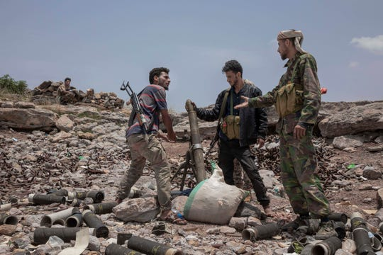 FILE - In this Monday, Aug. 5, 2019, file photo, fighters from a militia known as the Security Belt, that is funded and armed by the United Arab Emirates, discuss launching a mortar towards Houthi rebels, in an area called Moreys, on the frontline in Yemen's Dhale province. Saudi Arabia and the United Arab Emirates pledged Monday, Aug. 26, 2019, to keep their floundering coalition war against Yemen's Houthi rebels together after an Emirati troop pullout and the rise of the southern separatists they supported.