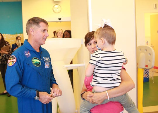 NASA astronaut Shane Kimbrough takes some time with with Izzy Caudill, 4, and her mother, Stephanie Caudill, 31, of Milan at an event at C.S. Mott Children's Hospital at the University of Michigan on Thursday.