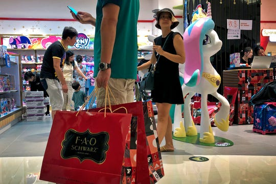 In this June 1, 2019, photo, file a man carries a paper bags containing toys purchased from the FAO Schwarz as people shop at the newly open FAO Schwarz toy store at the capital city's popular shopping mall in Beijing. Caught in the crossfire of a trade war, American businesses operating in the China say they've been hurt by the hostilities between the world's two biggest economies and are facing increasingly unfair competition from Chinese firms.