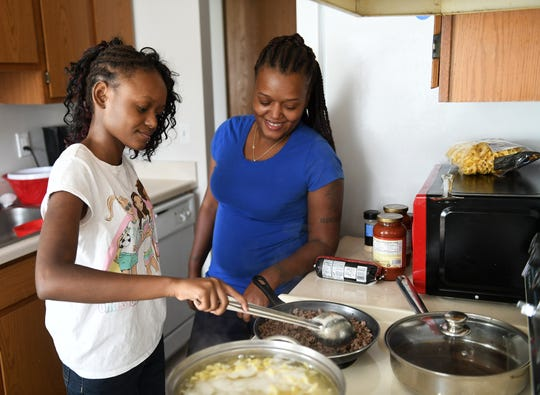 Monet Shaw helps her mother, Patrice Shaw, make dinner at their home in Clinton Township. Monet's family recently shared her story of survival.