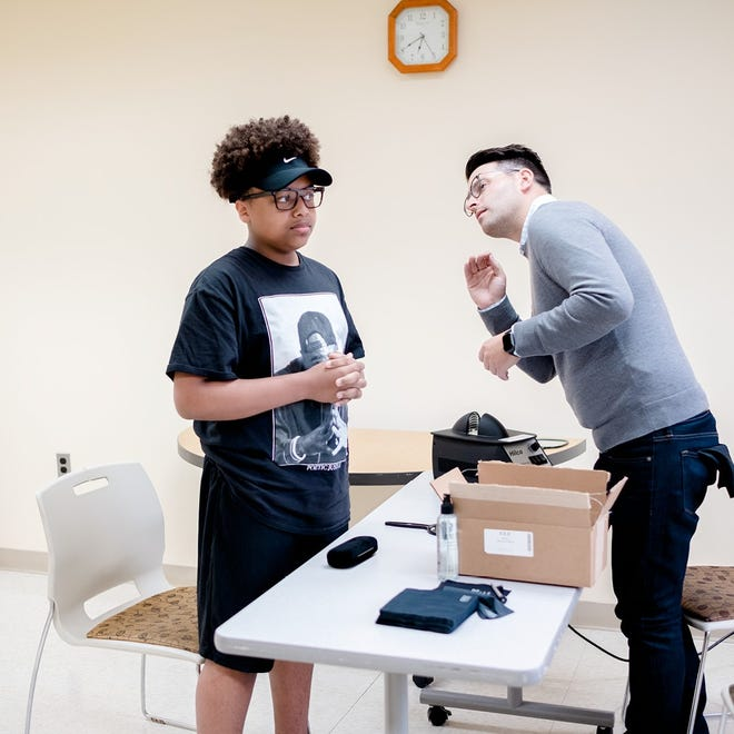 CJ Pitt, left, from Detroit Youth Choir gets fitted for new glasses by Andrew Stinson from See Eyewear.