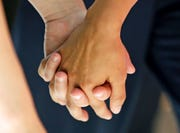 """In this Wednesday, July 15, 2015 file photo, a lesbian couple holds hands in Salt Lake City. Released on Thursday, Aug. 29, 2019, the largest study of its kind found new evidence that genes contribute to same-sex sexual behavior, echoing research that says there is no single """"gay gene."""""""