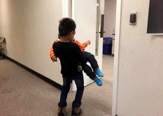 This Tuesday, Aug. 27, 2019 photo, a 7-year-old boy from Mexico  carries his 2-year-old sister into a playroom at a migrant shelter affiliated with the San Diego Rapid Response Network in San Diego. They are seeking asylum with their mother.  Registration forms at the San Diego shelter for asylum-seeking families offer insights on who is coming, how they are treated in U.S. custody and where they go. Houston was the most popular destination by far, a reflection of its emergence as a primary gateway for immigrants.
