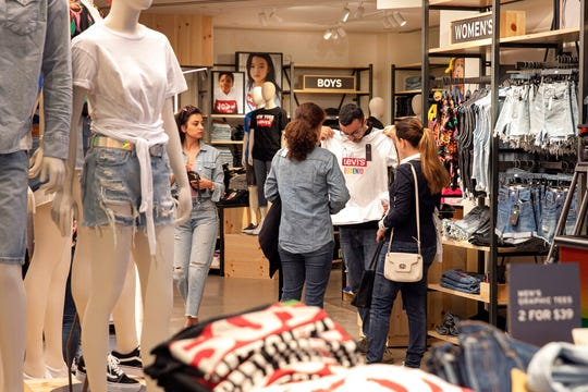 In this June 14, 2019, file photo a customers shop in the Levi's store, in New York's Times Square. The U.S. economy slowed in the spring, and most analysts expect it to weaken further in the months ahead. Yet the main driver of growth, consumer spending, remains vigorous enough to keep the economy growing steadily if still modestly.