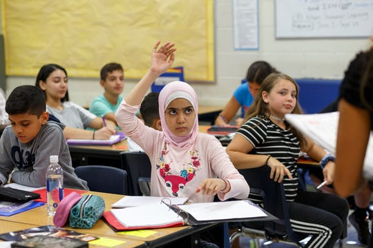 Fatima Alzihairy, 11, of Dearborn, raises her hand to ask a question during sixth-grade math class at Bryant Middle School on Thursday.