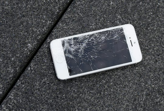 An Apple iPhone with a cracked screen.