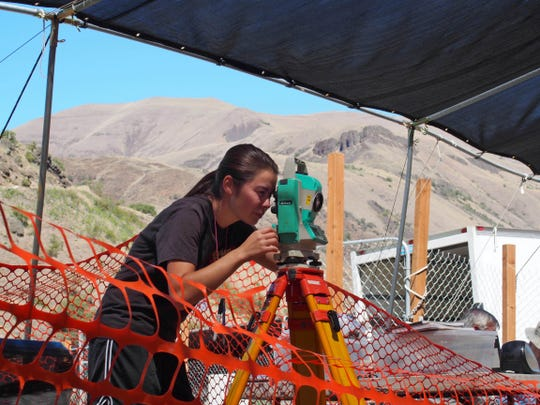 A researcher taking measurements at the Cooper's Ferry canyon archaeological site in western Idaho in 2015.