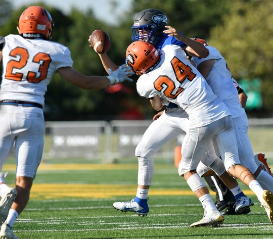 Brother Rice's Ohannes Sarkisian (24) and Cameron Terrill, rear, sack Eisenhower quarterback Blake Rastigue in the third quarter.