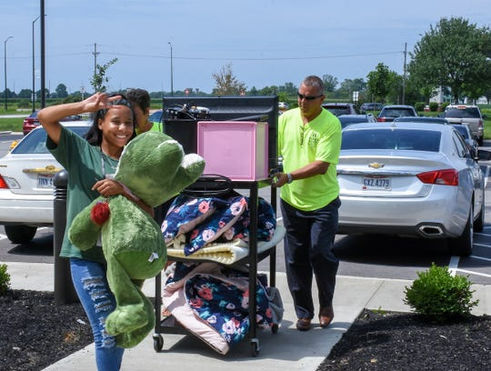 Terra State Community College President Dr. Ron Schumacher helps a student move into The Landings at Terra Village. The student housing facility has 157 occupants for the fall 2019 semester.