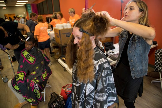 Kirsten Giles gets a haircut from Gabriela Garcia, right, at the Dream Center after attending a job fair in Fort Myers on Thursday, August 29, 2019. ÒI got all the information I need to send off my resumes to get a good job, and now IÕm going to get a good haircut,Ó Giles said.