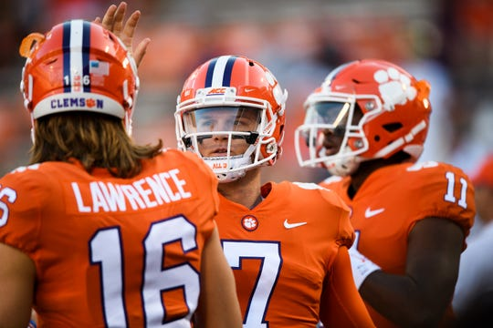 Clemson quarterback Trevor Lawrence (16) and Clemson quarterback Chase Brice (7) greet one another on the field during warmups before their game against Georgia Tech at Memorial Stadium Thursday, Aug. 29, 2019.