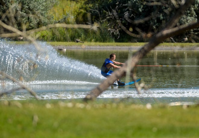 A water skier carves big turns on the glassy surface of the Missouri River, up stream from Broadwater Bay in Great Falls, recently.
