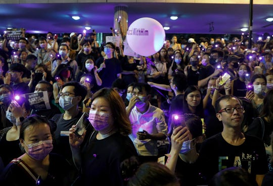 People flash their smartphones lights as they take part in a rally Wednesday at the financial district in Hong Kong. Several thousand people gathered to protest against what they called sexual violence by the police