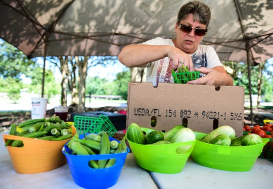 Effie Bryant, Bryant Produce, organizes okra into baskets to sell Aug. 29, 2019.