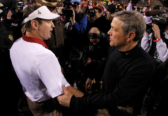 Oklahoma head coach Bob Stoops and Iowa head coach Kirk Ferentz meet on the field after the Insight Bowl in December 2011. The two will be in the same building again Saturday, as Stoops is Iowa's honorary captain for Week 1.