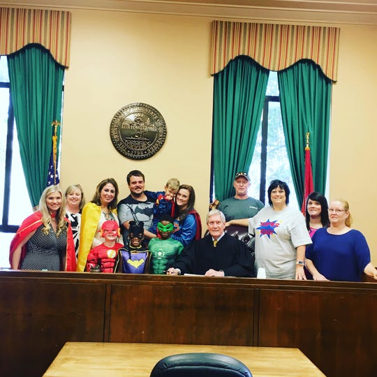 Surrounded by family and adoption personnel, the Jennings family poses with Chancellor James Butler at Madison County Chancery Court in honor of Casen Jennings' adoption Aug. 23, 2019.
