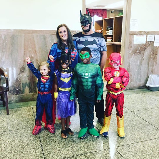 The Jennings family (Casen, Keely, Wes, Hayden, mom Candace and dad Ryan) strike superhero poses in Madison County Chancery Court in honor of Casen's adoption Aug. 23, 2019.