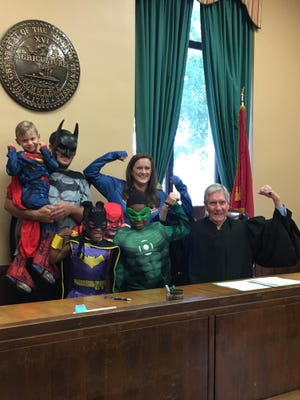 The Jennings family (Casen, Keely, Hayden, Wes, mom Candace and dad Ryan) show off their superhero muscles in Madison County Chancery Court with Chancellor James Butler in honor of Casen's adoption Aug. 23, 2019.