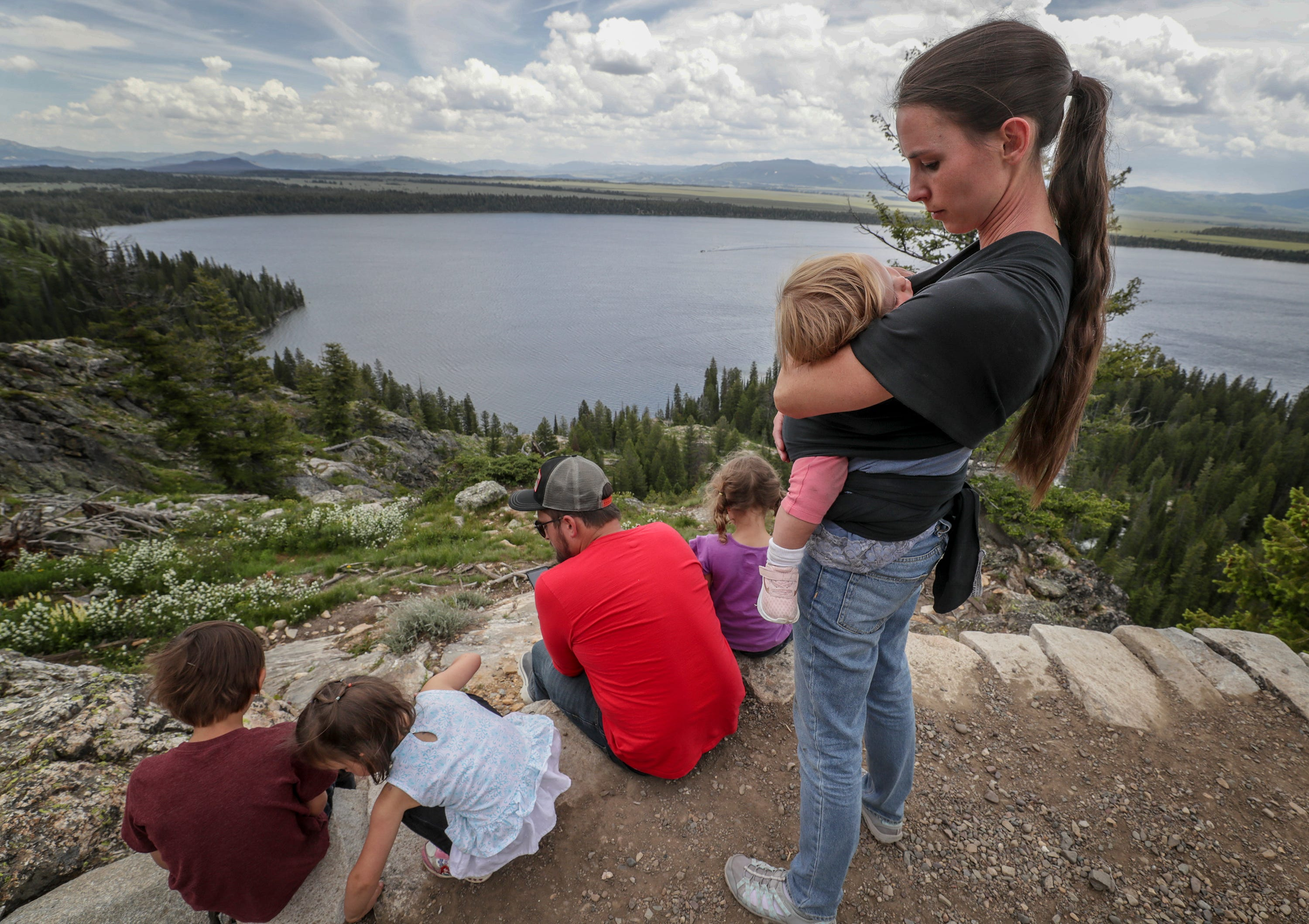 Rachael Denhollander holds her daughter, Elora, as her husband, Jacob, reads the Hobbit to their children at Inspiration Point in Tetons National Park in Wyoming.  Rachael and her family also visited the Tetons when she was a teenager and her father read the Hobbit to them as well.