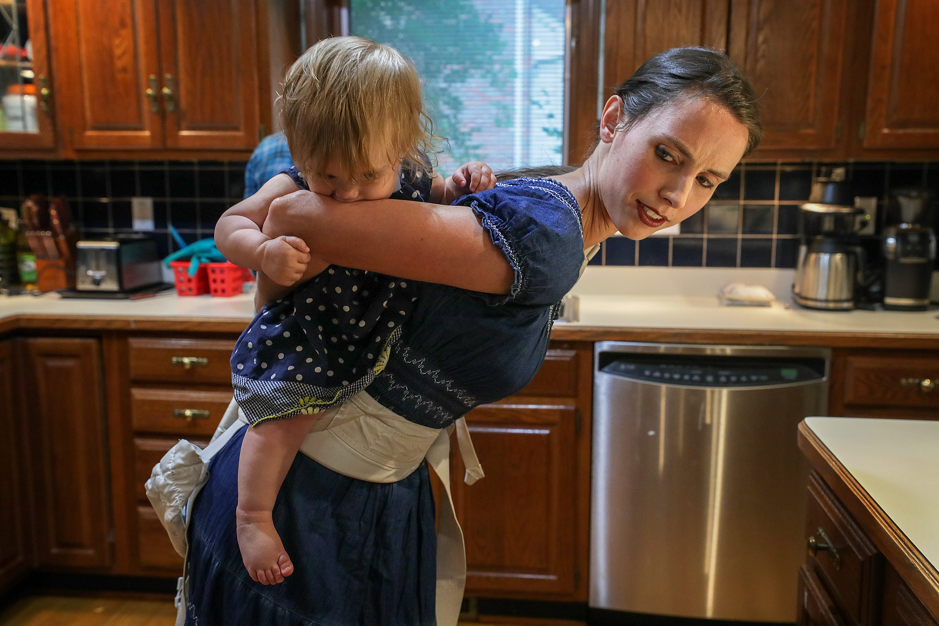 Rachael Denhollander straps her daughter, Elora, onto her back so that she can bake a cake with her other children at their former home in Louisville. May 2019