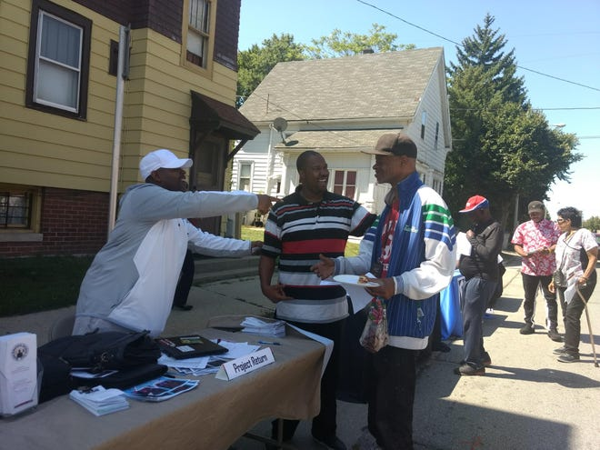 Eugene Nelson, left, and Andre Brown, middle, of Project Return greet one of the fair's participants.