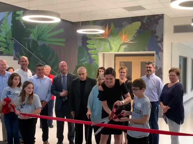 Silver Spring Intermediate School principal Deanne Wellens and a soon-to-be Silver Lake Intermediate School student Jack McCord cut the ribbon while other students, district officials and JP Cullen representatives look on.