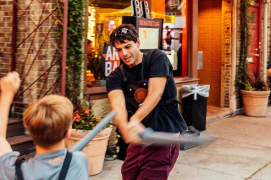 Inventor/business owner Adam Cohen swipes a foam sword at a kid opponent. One of the inventors of MagneTag, a cross between laser tag and sword-fighting, he has his sights set on opening a sports and recreation facility in East Tosa.