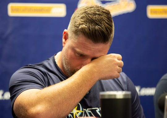 Montgomery Biscuits manager Morgan Ensberg wipes away tears during a news conference about pitcher Blake Bivens' wife and child who were killed in a triple homicide.