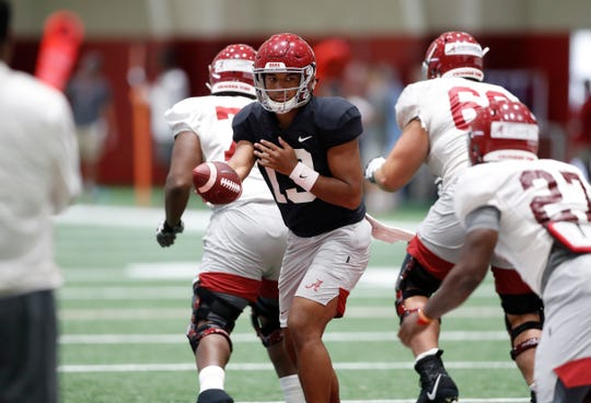Alabama junior quarterback Tua Tagovailoa looks to hand the ball off to redshirt freshman running back Jerome Ford during a recent practice inside the team's indoor facility on Aug. 28, 2019 in Tuscaloosa, Ala. (Photo by Robert Sutton/Alabama athletics)