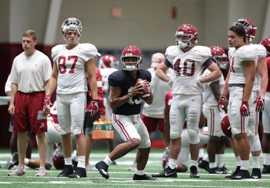 Alabama tight ends Miller Forristall (87), Giles Amos (40) and Cameron Latu (81) watch as quarterback Tua Tagovailoa (13) looks to throw a pass during a recent practice on Aug. 26, 2019 from the team's indoor practice facility in Tuscaloosa, Ala. (Photo by Kent Gidley/Alabama athletics)