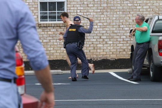 State Police chase Matthew Thomas Bernard after attacking Keeling Baptist Church groundskeeper Loyd Gauldin, right, on Tuesday, Aug. 27, 2019 in Keeling, Va.