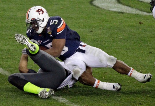 Auburn's Michael Dyer (5) rolls over Oregon's Eddie Pleasant as he carries the ball 37 yards during the BCS National Championship game Monday, Jan. 10, 2011, in Glendale, Ariz. Auburn won 22-19.