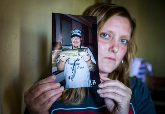 Erica Tackett hold a picture of her father, Rodney, who died of an overdose earlier this year.