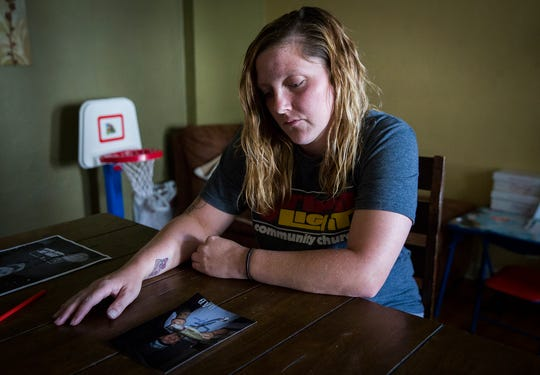 Erica Tackett looks at a picture of her father at her home in Muncie.