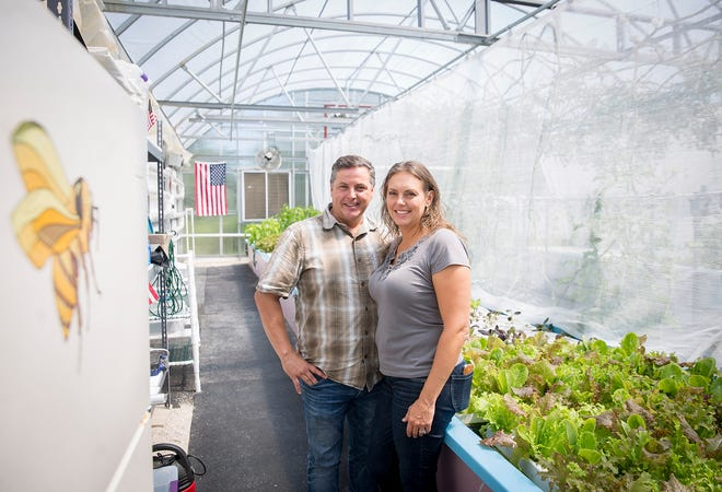 Glynn and Kellie Barber stand in a client's greenhouse in Daleville.