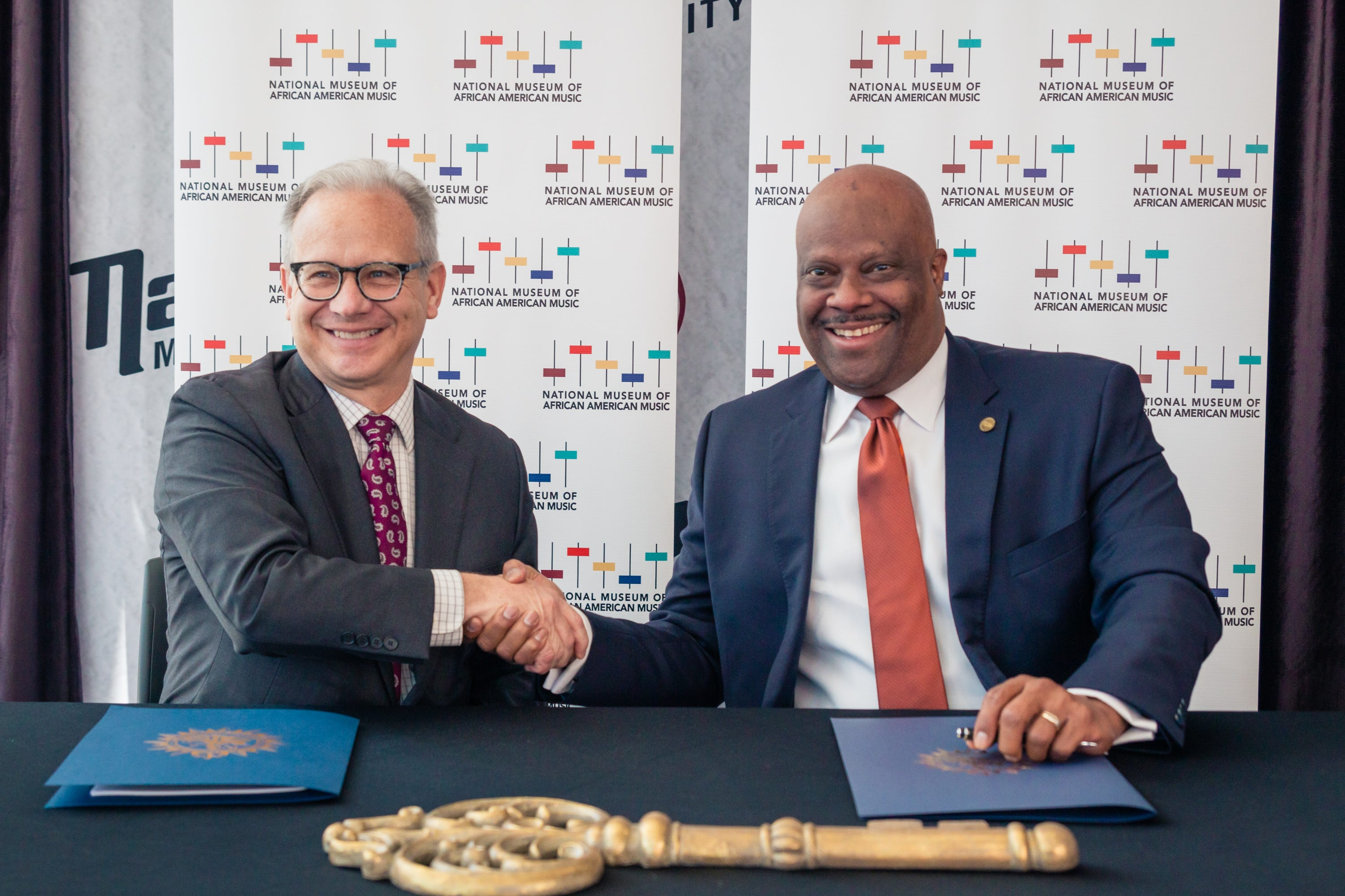 Former Nashville Mayor David Briley and National Museum of African American Music President and CEO H. Beecher Hicks III shake hands Aug. 29, 2019. Briley and Hicks signed a lease officially granting the museum control over its space in the Fifth + Broadway commercial development.