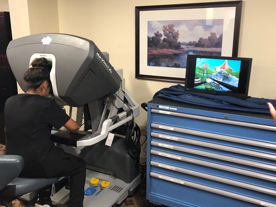 A HHS student works in a robotic surgery simulator.