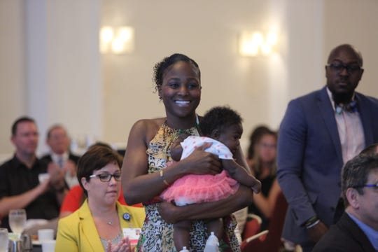 Kanema Clark, co-owner of Arc of Life Family Spinal Care, walks with her daughter to the stage at the Bonita Springs Chamber luncheon on Thursday.