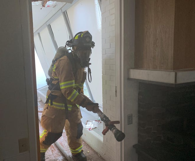 Newark firefighter Owen Rodeniser carries a hose inside the building located at 950 Sharon Valley Road during training on Thursday, Aug. 29, 2019. Newark Fire Department held training at the site of the future fire station ahead of demolition.