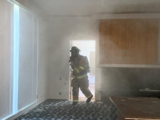 A Newark firefighter carries a hose inside the building located at 950 Sharon Valley Road during training on Thursday, Aug. 29, 2019. Newark Fire Department held training at the site of the future fire station ahead of demolition.