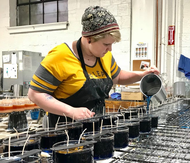 Sam Shiveler, an employee of Whiskey River Soap Company, makes candles at the business' West Main Street location.