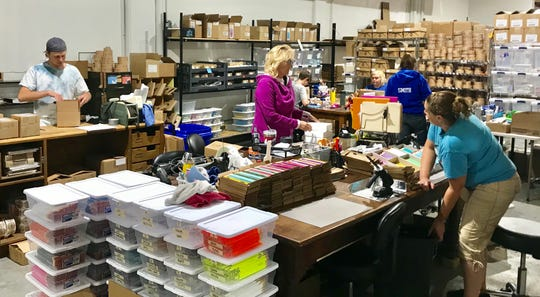 Whiskey River Soap Company employees work in the business' labeling, packaging and shipping department.