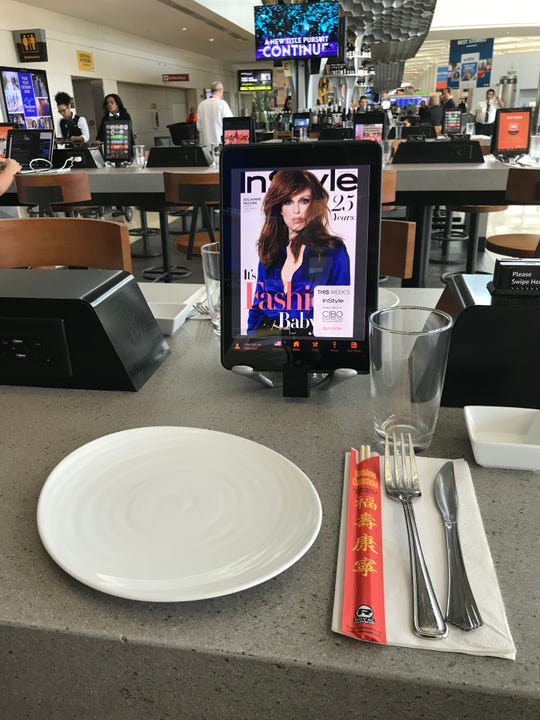 The seats at Newark Airport's Terminal C come equipt with iPads to order your food with.